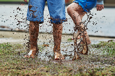 Buy stock photo Low angle shot of two unrecognizable children jumping around in mud outside during a rainy day