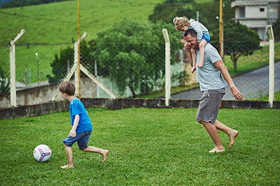 Buy stock photo Shot of a cheerful middle aged man carrying his daughter on his solders while playing soccer with his son outside during a cloudy day