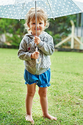 Buy stock photo Portrait of a cheerful little girl standing with an umbrella outside on a rainy day