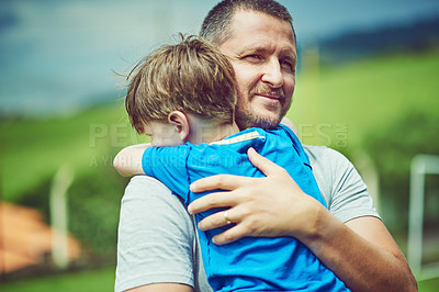 Buy stock photo Shot of a cheerful middle aged man holding his little boy in his arms outside during a cloudy day