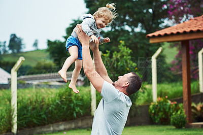 Buy stock photo Shot of a cheerful little girl being  lifted up in the air by her father outside during a cloudy day