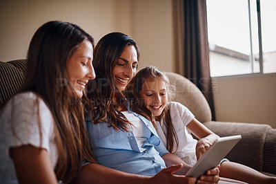 Buy stock photo Cropped shot of an attractive mother watching movies on a tablet with her two daughters at home