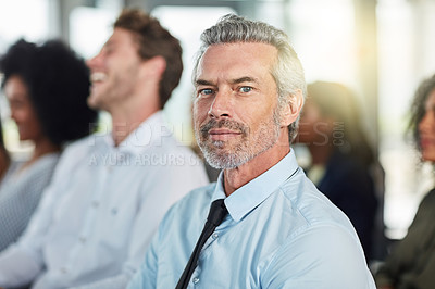 Buy stock photo Cropped portrait of a handsome mature businessman attending a seminar with his colleagues