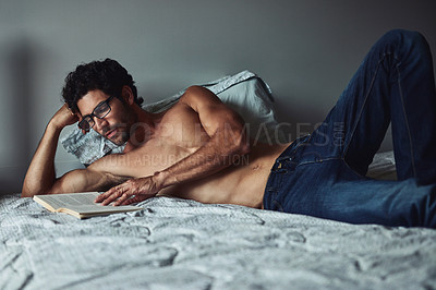 Buy stock photo Cropped shot of a handsome young shirtless man reading a book on his bed at home