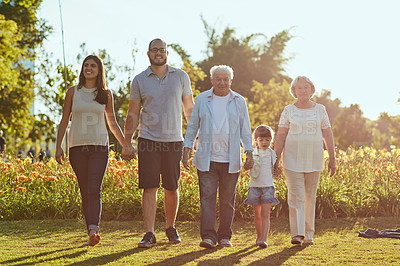 Buy stock photo Shot of a happy family going for a walk together in the park