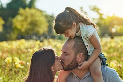 Buy stock photo Shot of an adorable little girl watching her parents kiss during a family bonding session in the park