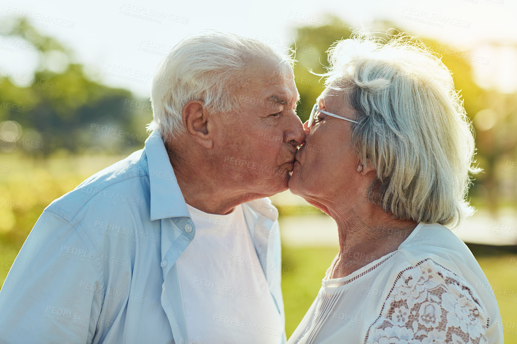 Buy stock photo Shot of a happy senior couple sharing a loving kiss in the park