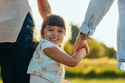 Buy stock photo Portrait of an adorable and happy little girl holding her mother and father's hands in the park