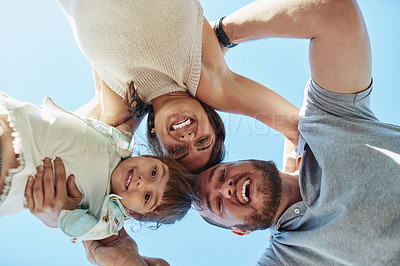 Buy stock photo Low angle portrait of a happy family huddled together outdoors