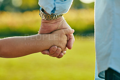 Buy stock photo Cropped shot of a little girl holding an unrecognizable man's hand in the park
