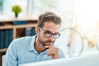 Buy stock photo Shot of a young businessman working on a computer in an office