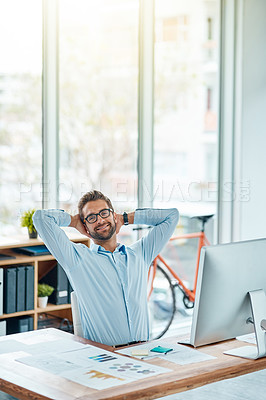 Buy stock photo Portrait of a young businessman taking a break while working in an office