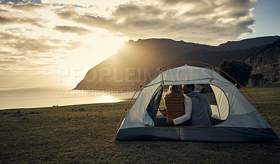 Buy stock photo Rearview shot of an affectionate young couple sitting in their tent while camping in the mountains