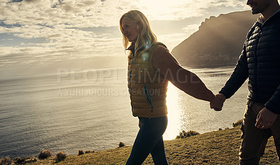 Buy stock photo Cropped shot of an affectionate young couple hiking in the mountains