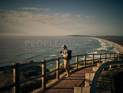 Buy stock photo Shot of a young man taking photos of the scenic landscape along the coast