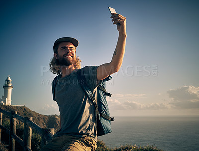 Buy stock photo Shot of a handsome young man taking selfies while out on a hike