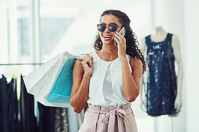 Buy stock photo Shot of an attractive young woman on a call while on a shopping spree in a boutique
