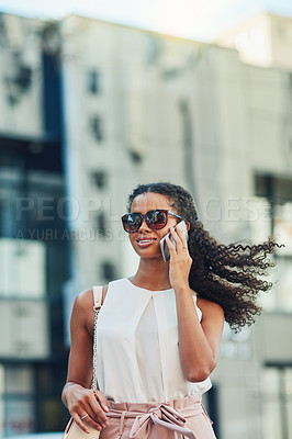 Buy stock photo Shot of an attractive young woman on a call in the city