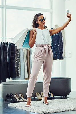 Buy stock photo Shot of an attractive young woman taking a selfie while on a shopping spree in a boutique