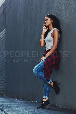 Buy stock photo Shot of an attractive young woman on a call posing against a wall in the city