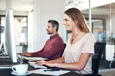 Buy stock photo Shot of a young businesswoman and businessman sitting next to each other and using their computers in a modern office