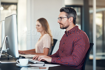 Buy stock photo Shot of a mature businessman sitting next to his colleague and using a computer in a modern office