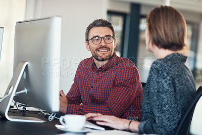 Buy stock photo Shot of a businessman and businesswoman having a conversation in a modern office
