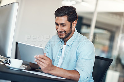 Buy stock photo Shot of a young businessman using a digital tablet at his desk in a modern office