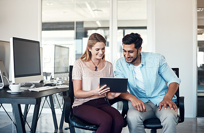 Buy stock photo Shot of a businessman and businesswoman using a digital tablet together in a modern office