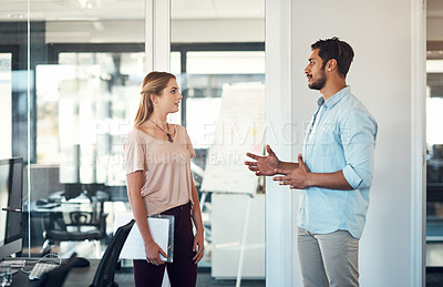 Buy stock photo Shot of a businessman and businesswoman having a discussion in a modern office