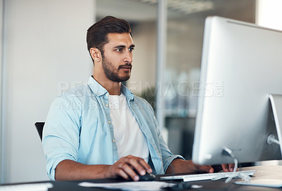 Buy stock photo Shot of a handsome young businessman using a computer at his desk in a modern office