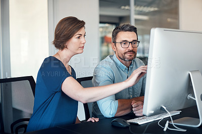 Buy stock photo Shot of a businessman and businesswoman using a computer together in a modern office