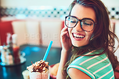 Buy stock photo Cropped shot of an attractive young woman enjoying a milkshake in a retro diner
