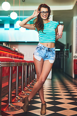 Buy stock photo Full length shot of an attractive young woman enjoying a milkshake while standing in a retro diner