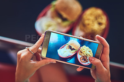 Buy stock photo High angle shot of an unrecognizable young woman taking photos of her burger in a retro diner