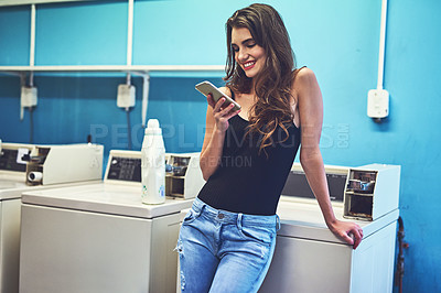Buy stock photo Shot of an attractive young woman texting on her phone while she does her washing inside of a laundry room during the day