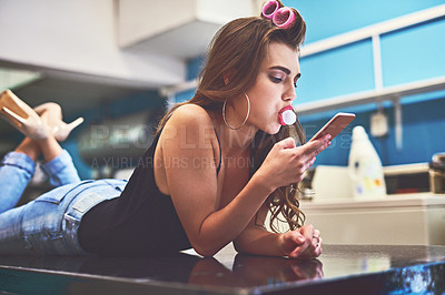 Buy stock photo Shot of an attractive young woman lying on top of a counter while browsing on a cellphone to pass time in a laundry room