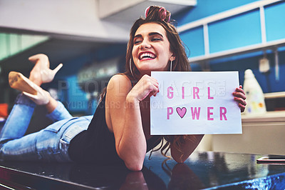 Buy stock photo Shot of an attractive young woman lying on top of a counter while holding a sign saying