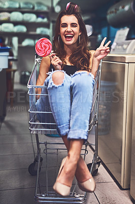 Buy stock photo Portrait of an attractive young woman seated inside of a shopping cart while holding a lollipop and showing the peace sign inside of a laundry room