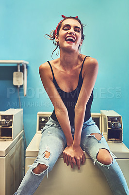 Buy stock photo Portrait of an attractive young woman seated on a washing machine while waiting for the washing to be washed inside of a laundry room