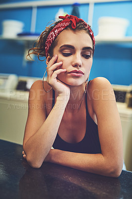 Buy stock photo Shot of an attractive young woman resting her arms on a counter while waiting for her washing to wash inside of a laundry room