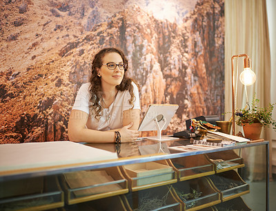 Buy stock photo Shot of an attractive young woman working at the counter of a store