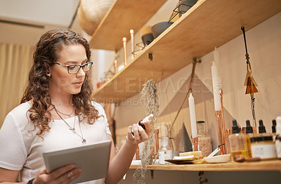 Buy stock photo Shot of a young woman using a digital tablet while working in a store
