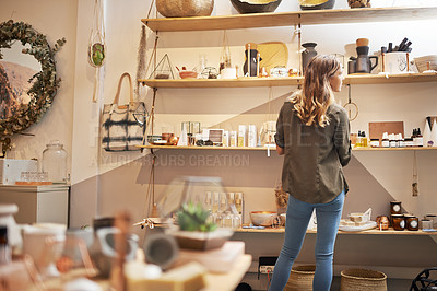 Buy stock photo Rearview shot of a young woman looking at products on a shelf in a store