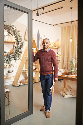 Buy stock photo Shot of an entrepreneurial young man standing by the open door of a store