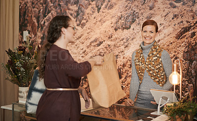 Buy stock photo Shot of a young woman purchasing goods from a boutique owner