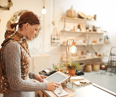 Buy stock photo Shot of an attractive middle aged woman working at the counter of a store