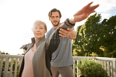 Buy stock photo Shot of a senior woman practicing yoga with a male instructor at home