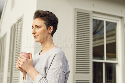 Buy stock photo Cropped shot of an attractive young woman relaxing with a cup of coffee at home