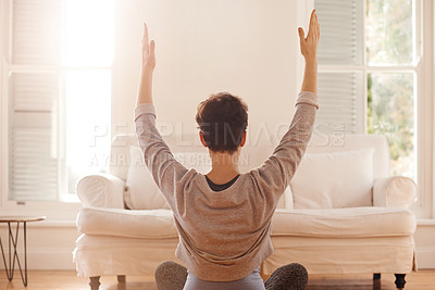 Buy stock photo Rearview shot of an unrecognizable woman practicing yoga in the living room at home